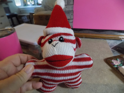 Sock monkey star shaped plush wearing Santa Hat