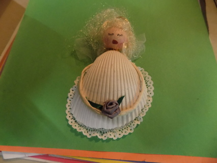 5 inch tall angel made of seashells blonde hair and hold purple rose