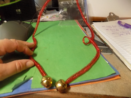 36 inch long red metallic tube trim with golden jingle bells end
