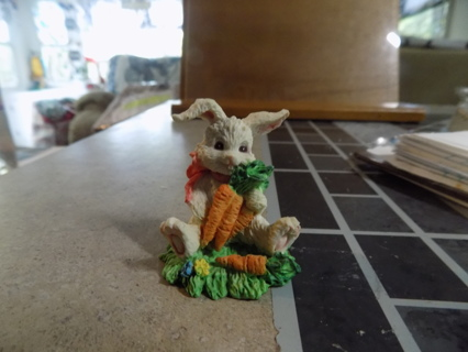 Resin textured bunny holds bunch of carrots and has pink bow