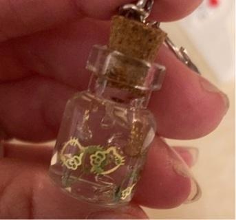 Mini corked glass jar with gold hello kitty's inside.
