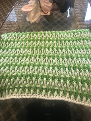 green and white crocheted baby blanket