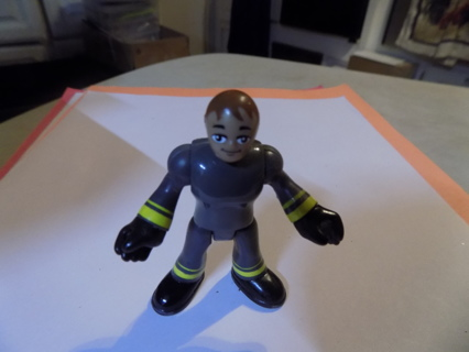 2 1/2 tall poseable figure brown hair dresed in gray suit with yellow stripe & black boots
