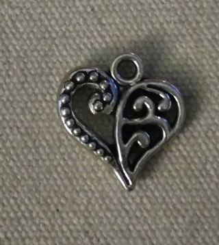 One silver tone filigree heart charm. Use the get it now option and get a free surprise.