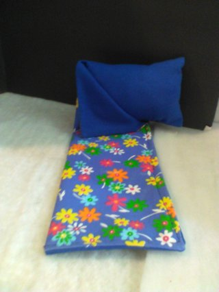 Barbie sleeping bag with blue background and flowers.