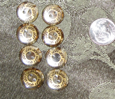 8 small clear buttons with gold accent and black joff written on top