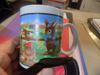 Ceramic coffee cup with girl & boy bunny at a fence